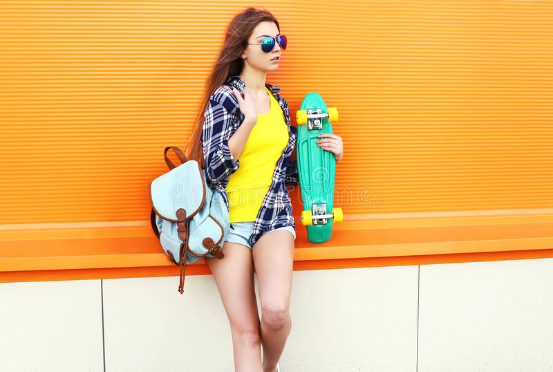 Fashion pretty cool girl wearing a sunglasses and backpack with skateboard over orange stock photo