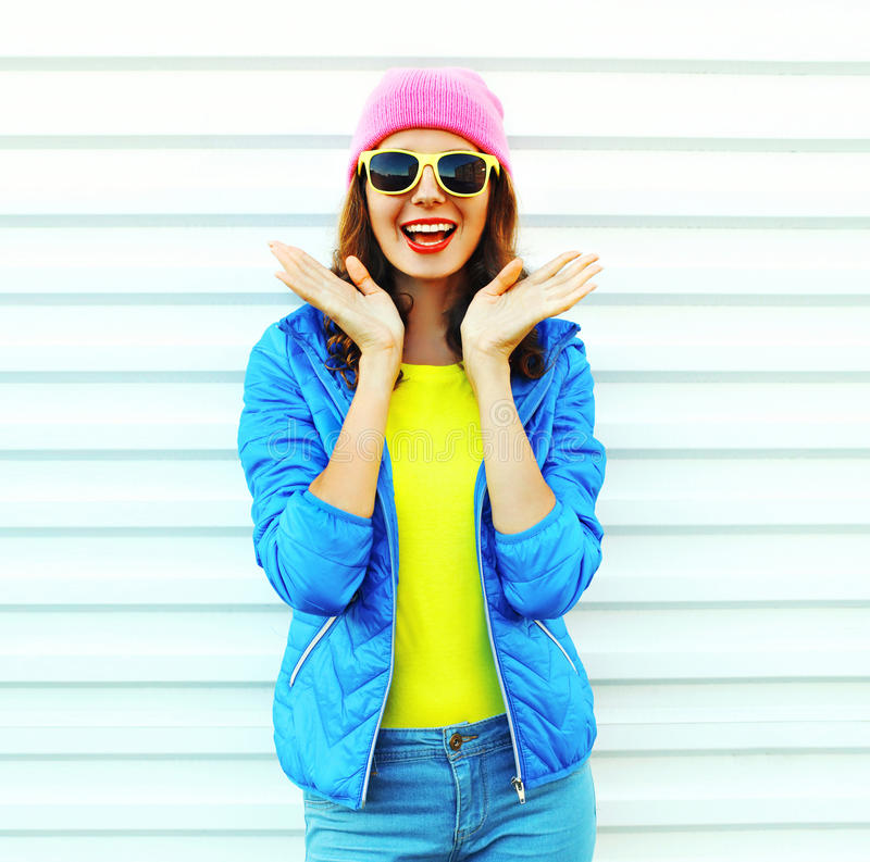 Fashion pretty cool shocked woman in colorful clothes having fun over white background wearing a pink hat yellow sunglasses royalty free stock photos