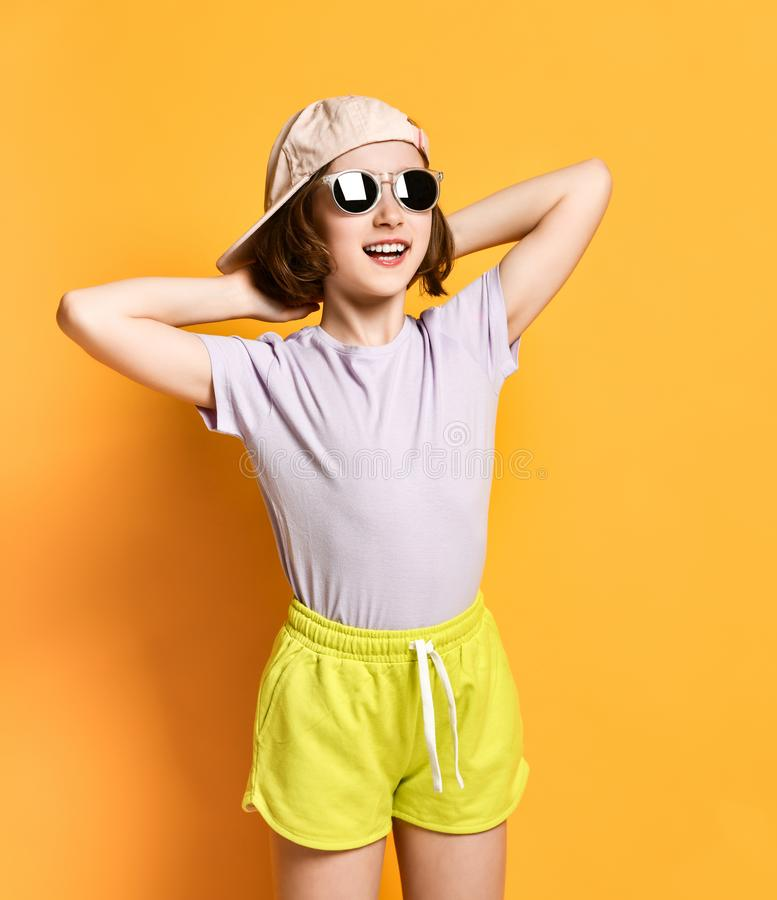 Fashion pretty cool teenager girl in sunglasses and light cap, hat and shorts on a yellow background. royalty free stock photo