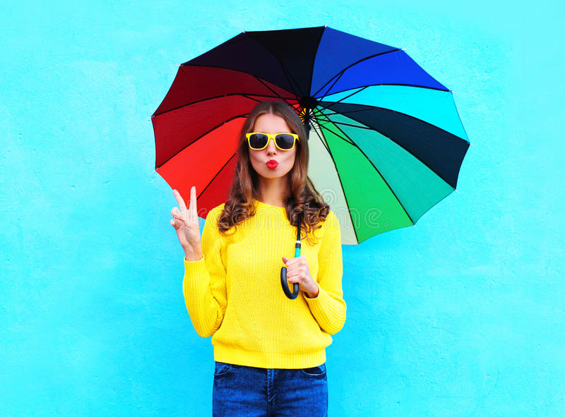 Fashion pretty cool woman holding colorful umbrella in autumn day over blue background wearing a yellow knitted sweater. Fashion pretty cool woman holding royalty free stock photography