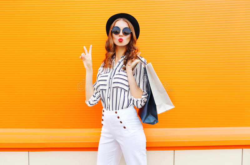 Fashion pretty cool young girl with shopping bags wearing a black hat white pants over colorful orange royalty free stock images