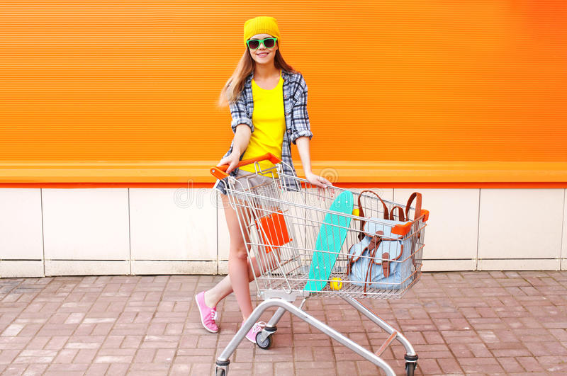 Fashion pretty girl with shopping trolley cart and skateboard over colorful orange stock image