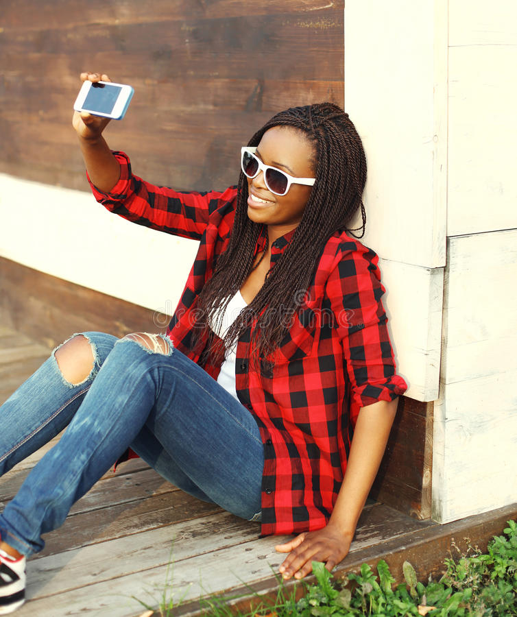 Fashion pretty smiling african woman makes self-portrait on smartphone. And having fun in city stock photo