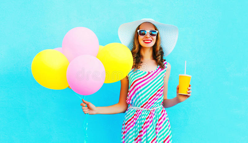 Fashion pretty smiling woman holds a fruit juice cup with an air colorful balloons stock photos