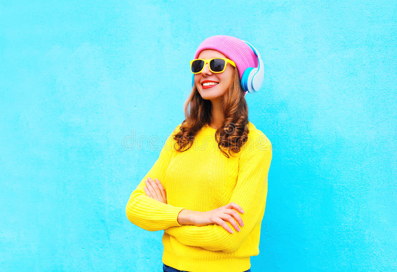 Fashion pretty smiling woman listens to music in headphones wearing a colorful pink hat, yellow sunglasses and sweater. Over blue background royalty free stock photos