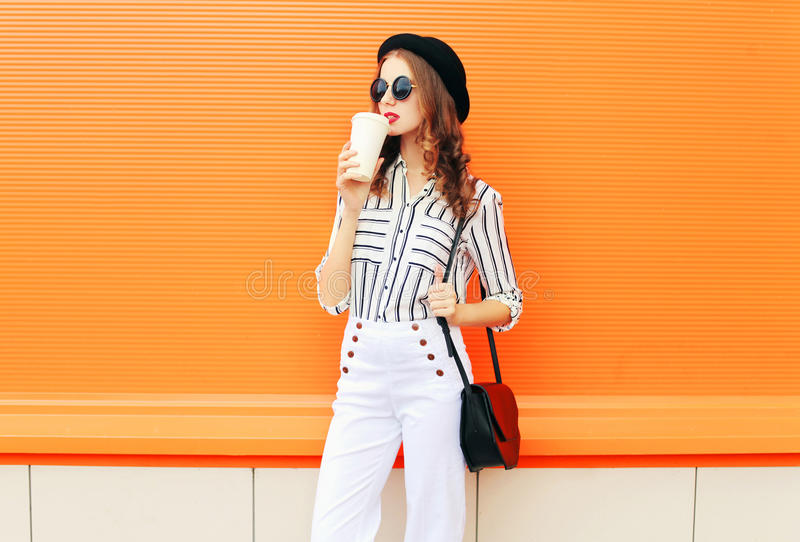 Fashion pretty woman with coffee cup wearing a black hat white pants handbag clutch over colorful orange. Background stock images