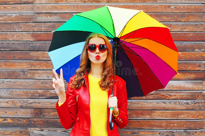 Fashion pretty woman with colorful umbrella in autumn day over wooden background wearing red leather jacket. Fashion pretty woman with colorful umbrella in royalty free stock image