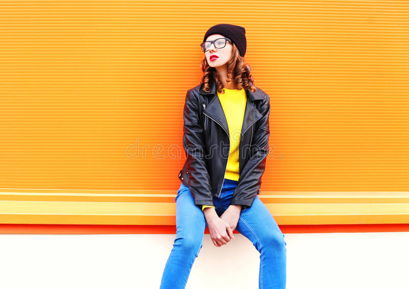 Fashion pretty woman model posing in black hat rock jacket over colorful orange background. Fashion pretty woman model posing in black hat and rock jacket over stock photography