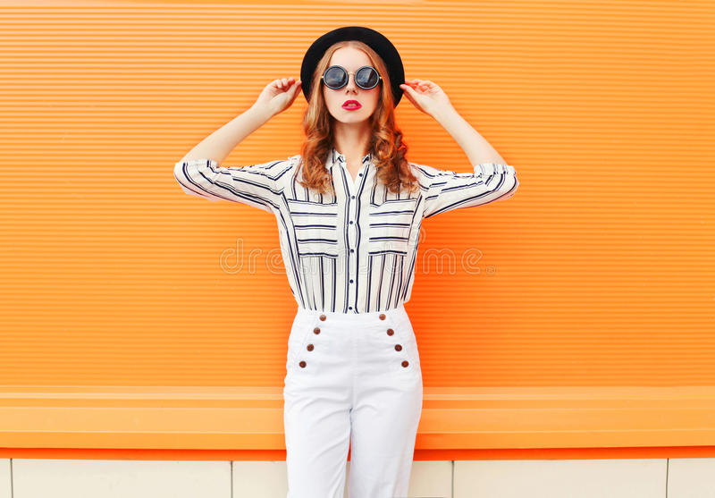 Fashion pretty woman model wearing black hat sunglasses white pants over colorful orange. Background stock image