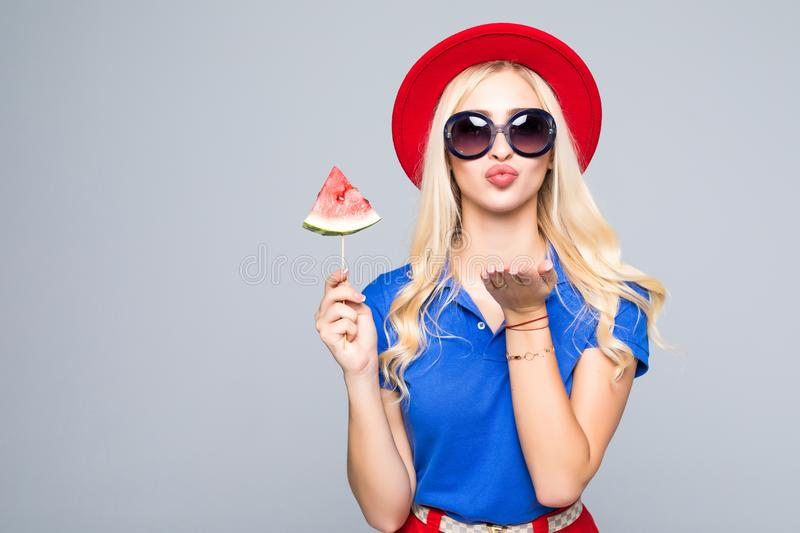 Fashion pretty woman sends an air kiss blowing red lips with a slice of watermelon colorful clothes isolated on gray background stock photography