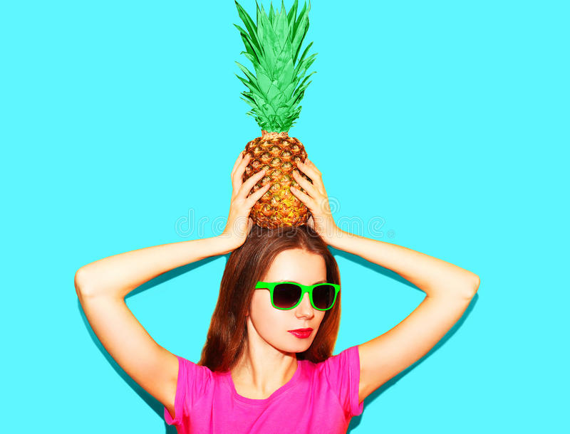 Fashion pretty woman in sunglasses with pineapple over blue stock image