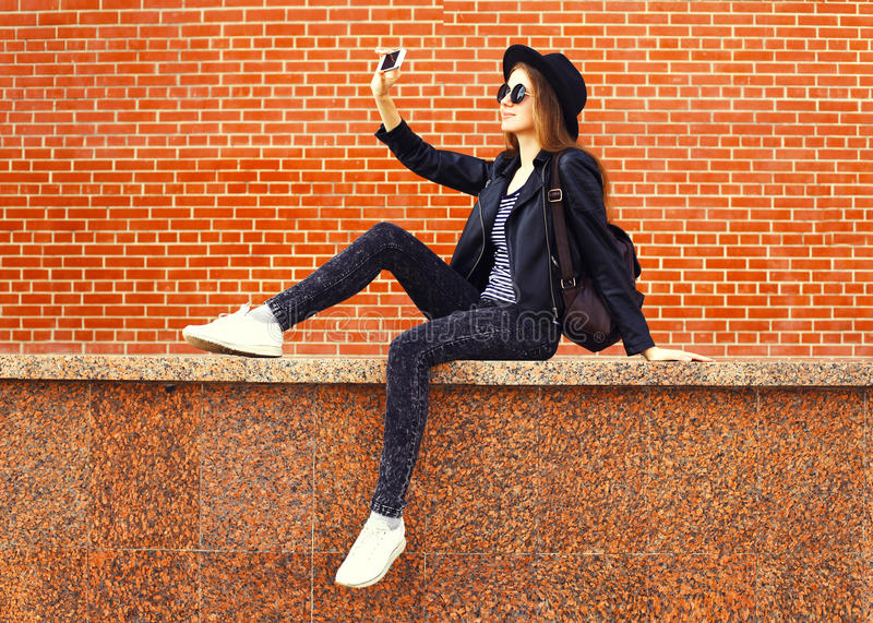 Fashion pretty woman taking photo picture self-portrait on smartphone in rock black style over bricks background. Fashion pretty woman taking photo picture self stock images