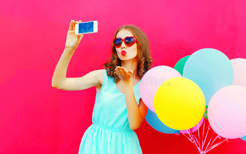 Fashion pretty woman taking a picture on a smartphone sends an air kiss over an air colorful balloons pink background stock image