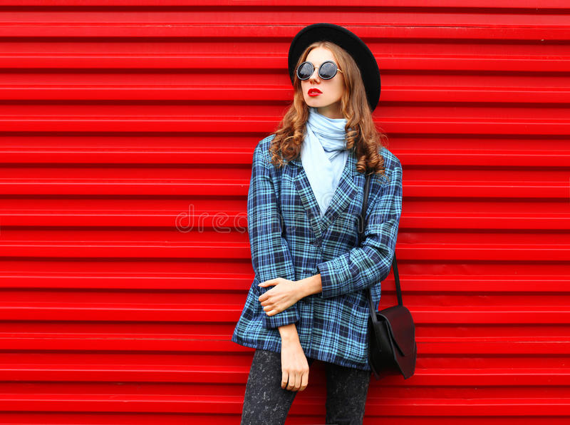 Fashion pretty woman wearing a black hat coat jacket and handbag over colorful red stock photos