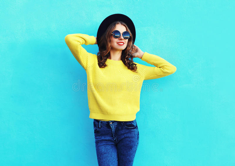 Fashion pretty woman wearing black hat and yellow knitted sweater over colorful blue. Background royalty free stock images