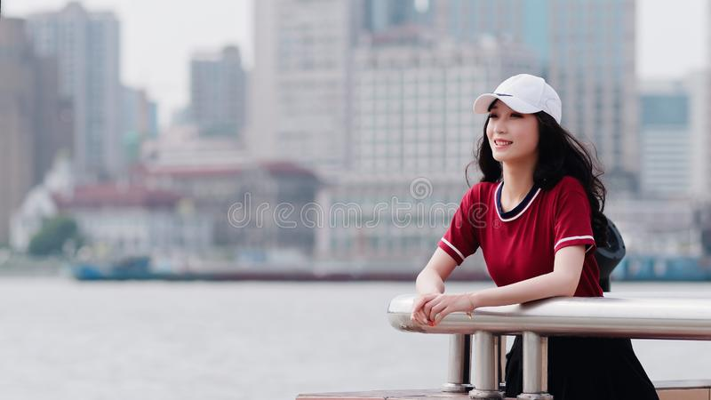 Fashion pretty young girl with black long hair, wearing red T-shirt and white baseball cap posing outdoor, minimalist urban clothi royalty free stock photos