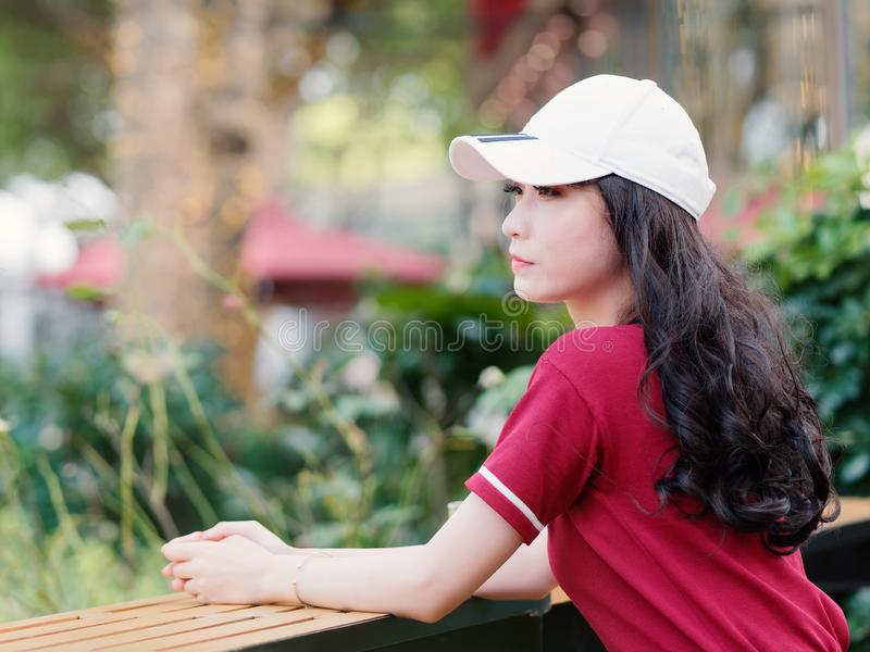 Fashion pretty young girl with black long hair, wearing red T-shirt and white baseball cap posing outdoor, minimalist urban clothi stock photo
