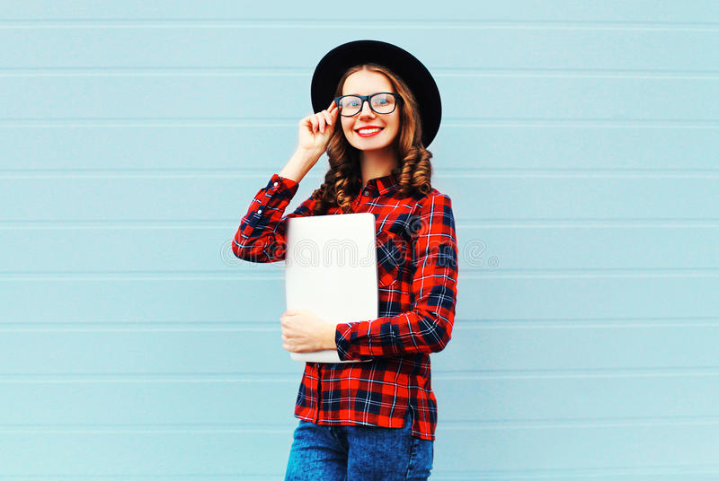 Fashion pretty young smiling woman holding laptop computer or tablet pc in city, wearing a black hat, red checkered shirt. Over blue background royalty free stock photography