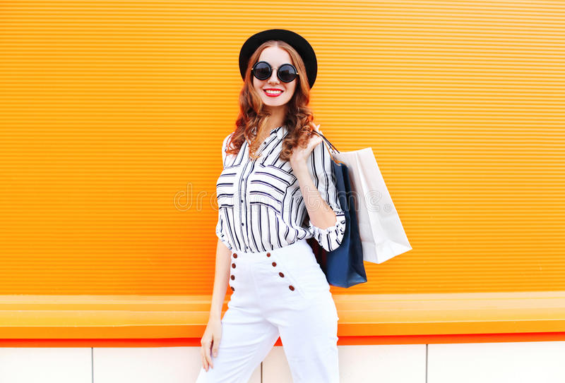 Fashion pretty young smiling woman model with shopping bags wearing a black hat white pants over colorful orange stock images