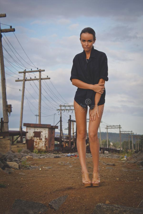 Fashion pretty young woman with long legs posing outdoor on the ground near a Electric poles. Beautiful brunette on heels only in stock photos