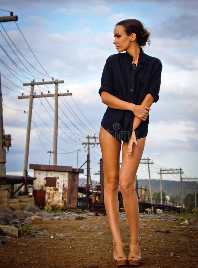 Fashion pretty young woman with long legs posing outdoor on the ground near a Electric poles. Beautiful brunette on heels only in royalty free stock image