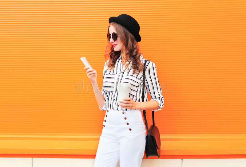 Fashion pretty young woman model using smartphone with coffee cup wearing black hat white pants over colorful orange. Background royalty free stock photo