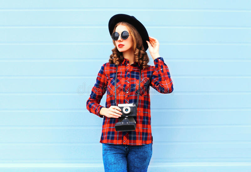 Fashion pretty young woman with retro camera posing wearing a black hat, red checkered shirt over blue background. Fashion pretty young woman with retro camera stock photos