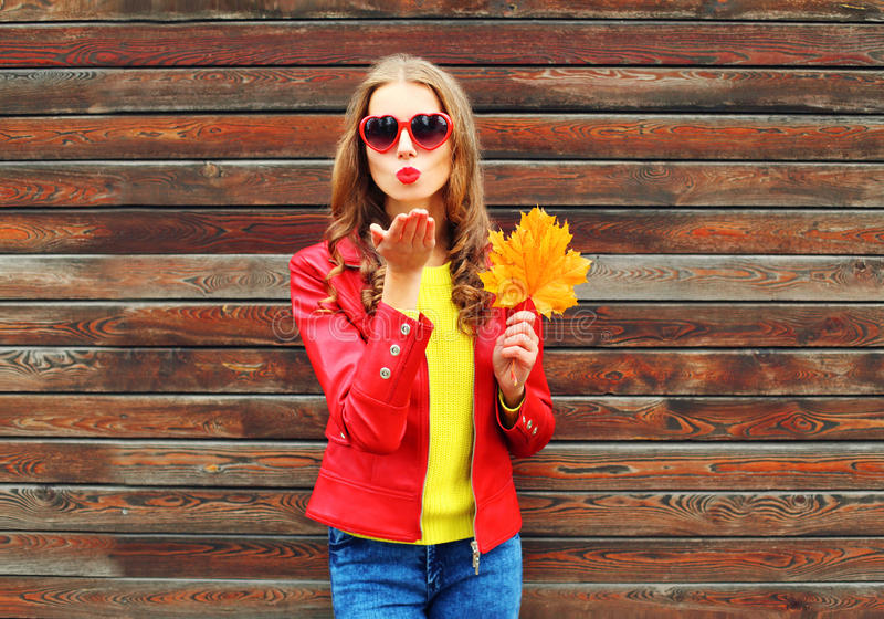 Fashion pretty young woman sends air sweet kiss with yellow maple leafs in autumn day over wooden background wearing red leather. Fashion pretty young woman royalty free stock image