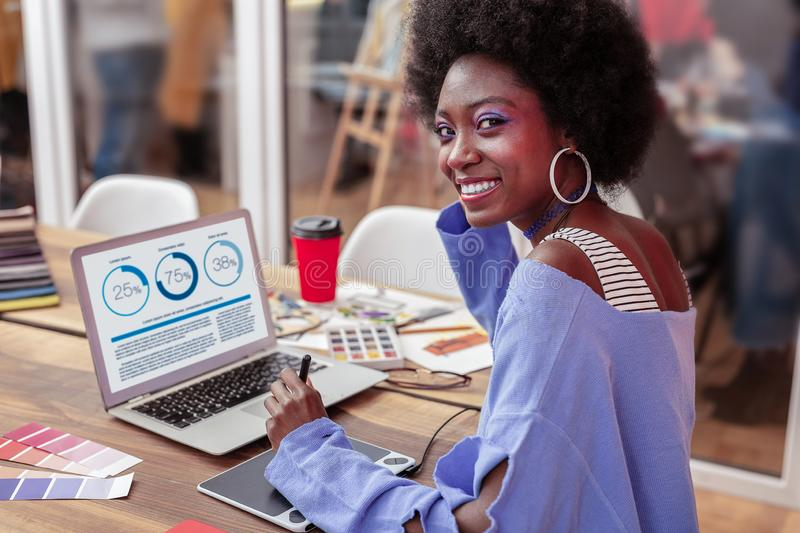 Manager of creative fashion project smiling while working. Fashion project. Beautiful cheerful manager of creative fashion project smiling while working royalty free stock photography