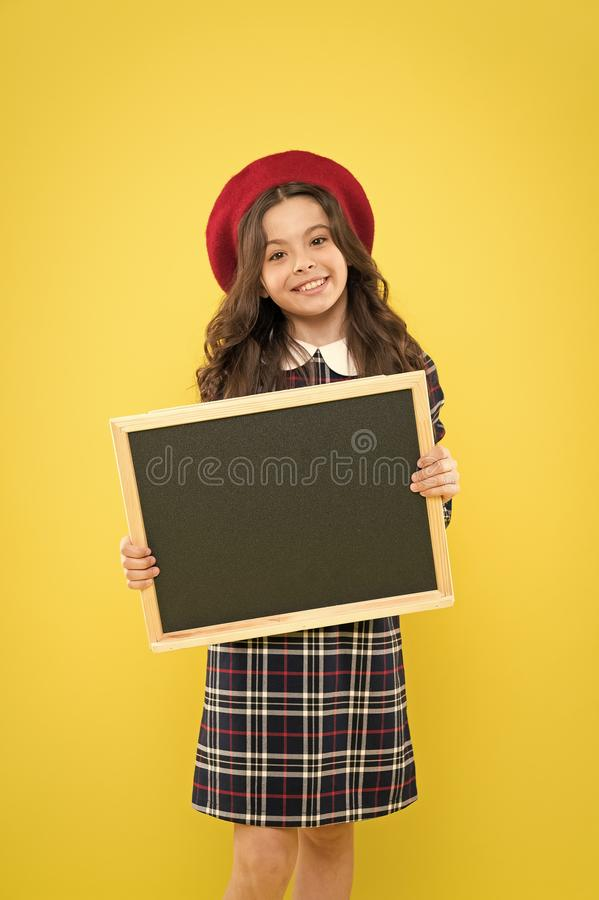 Fashion sales. parisian child on yellow background. happy girl with long hair in beret. small girl in french beret royalty free stock image