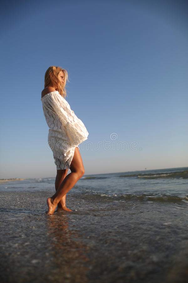 Fashion at the seasidea. Female in white summer dress walking in the sea royalty free stock photography