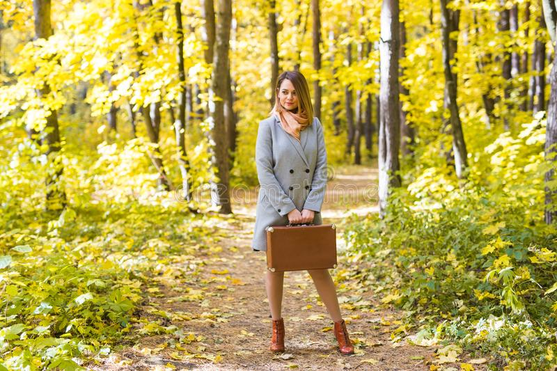 Fashion, season and people concept - happy young woman is going on a trip with retro suitcase on a background of autumn stock image