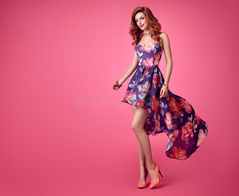 Fashion Sensual Redhead Girl. Summer Floral Dress. Sensual Redhead woman in Fashion Trendy Floral summer Dress Smiling. Beauty Model in fashion pose. Stylish royalty free stock image