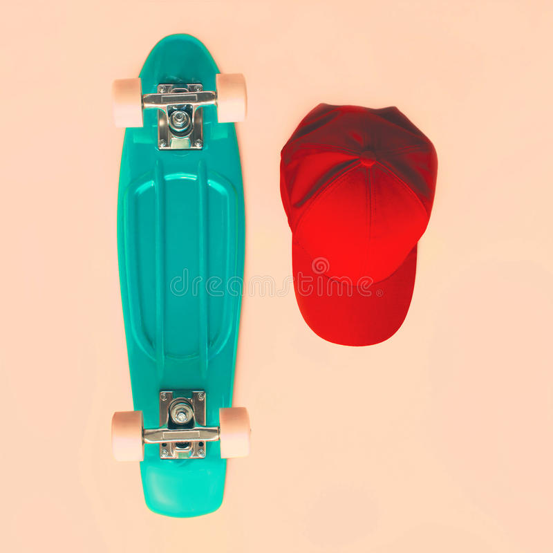 Fashion set. Skateboard and baseball cap on beige background, top view. Vintage hipster colorful photo royalty free stock photo