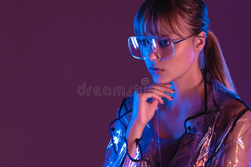 Fashion sexy woman wearing transparent raincoat eyewear at purple background. Fashion sexy young woman girl model attractive face wearing stylish trendy royalty free stock images