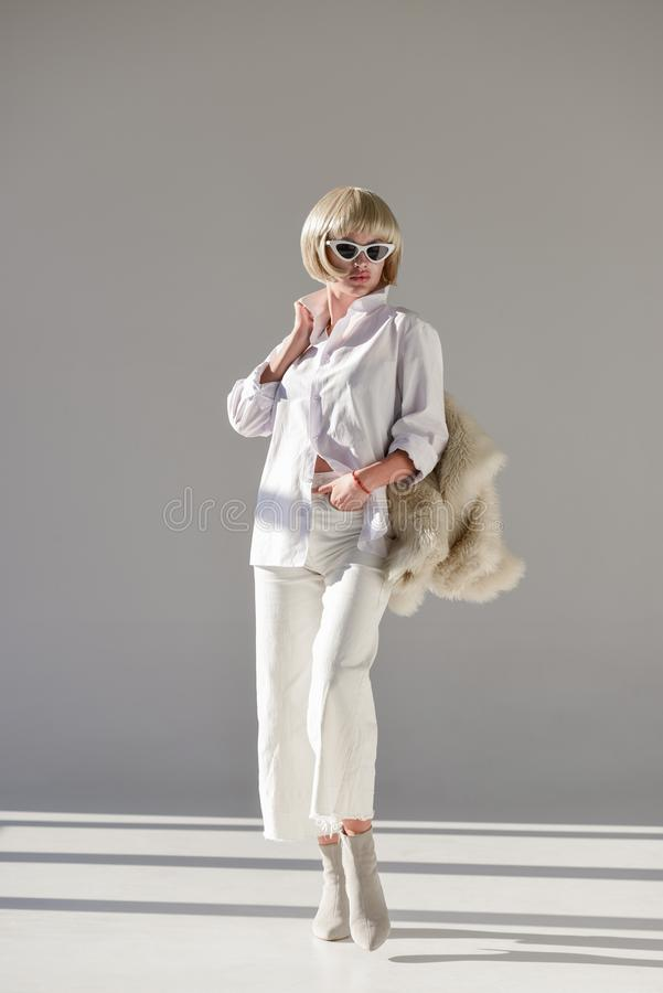 fashion shoot of attractive blonde woman standing in sunglasses and stylish winter outfit with faux fur coat stock photo