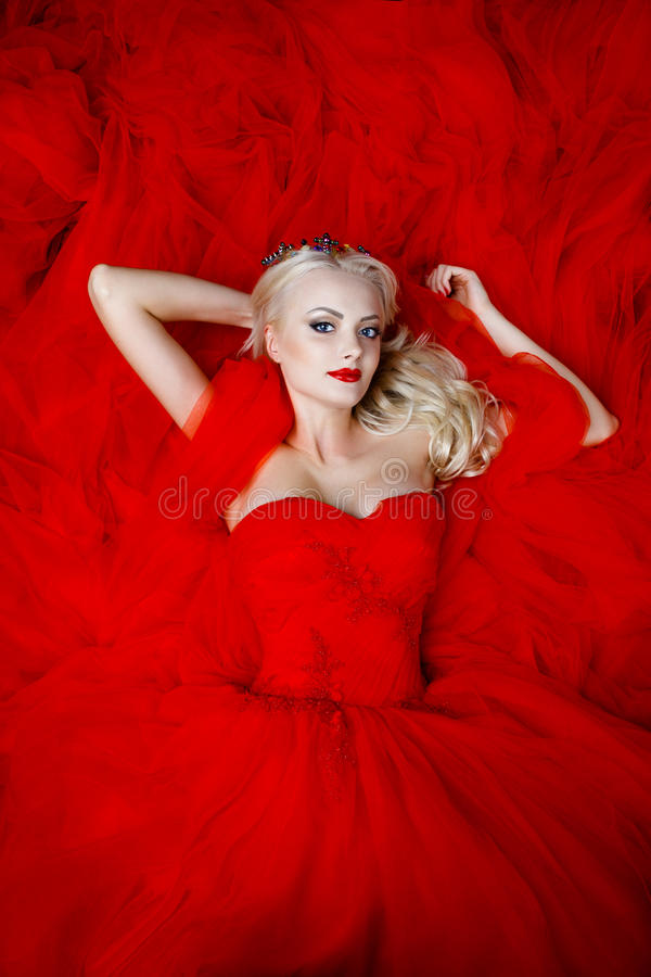 Fashion shoot of beautiful blond woman in a long red dress. Portrait of beauty young blond girl with red lips. Female face with clear skin close-up. Skincare royalty free stock photo