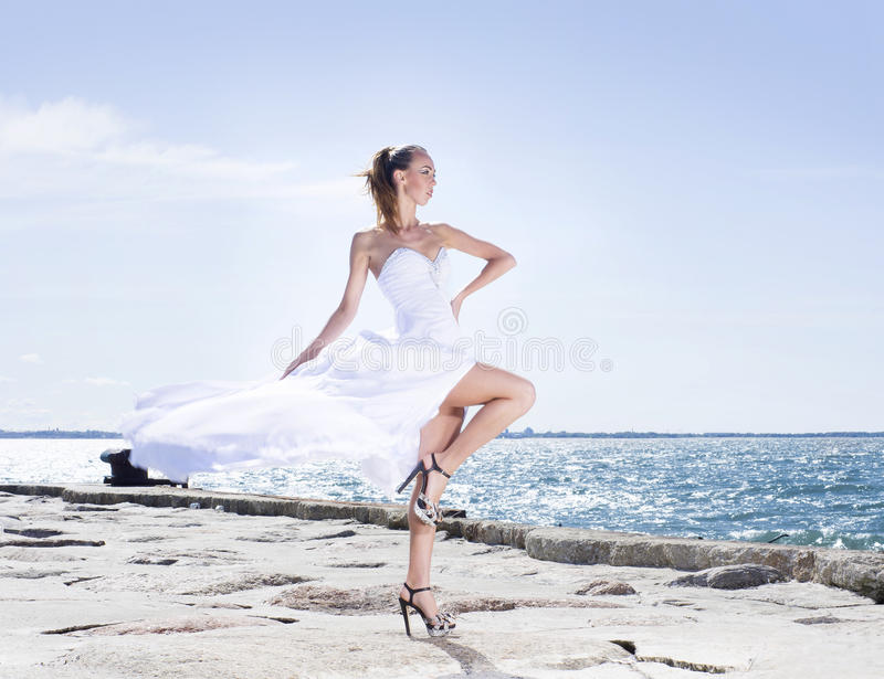 Fashion shoot of a young woman on a sea background stock photos