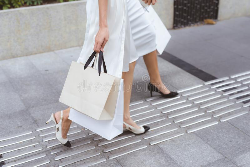 Fashion shopper woman legs with shopping bags in the street. Fashion shopper women legs with shopping bags in the street royalty free stock images