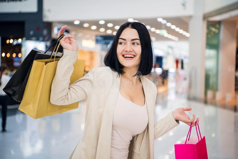 Fashion Shopping Girl Portrait. Beauty Woman with Shopping Bags in Shopping Mall. Shopper. Sales. Shopping Center. stock photos