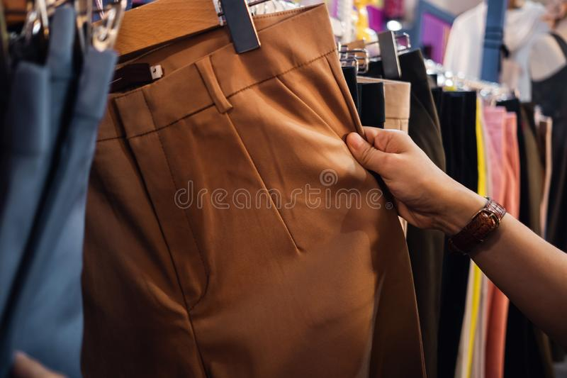 Fashion Shopping Lifestyle and Clothes for Women. Cropped image of Female Customer Choosing Pant. In Clothing Store royalty free stock images