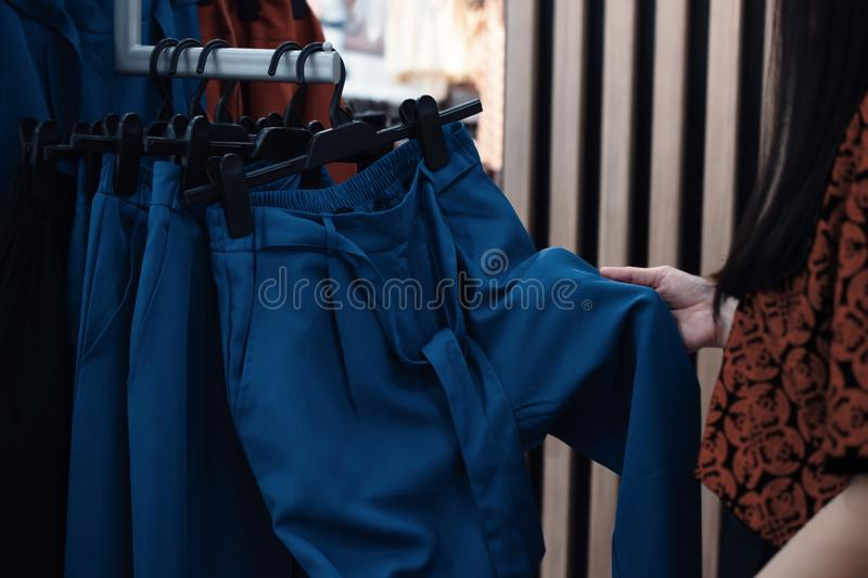 Fashion Shopping Lifestyle and Clothes for Women. Cropped image of Female Customer Choosing Pant. In Clothing Store royalty free stock photography
