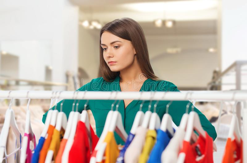 Woman choosing clothes at clothing store. Fashion, shopping and people concept - pensive woman choosing clothes in clothing store stock images