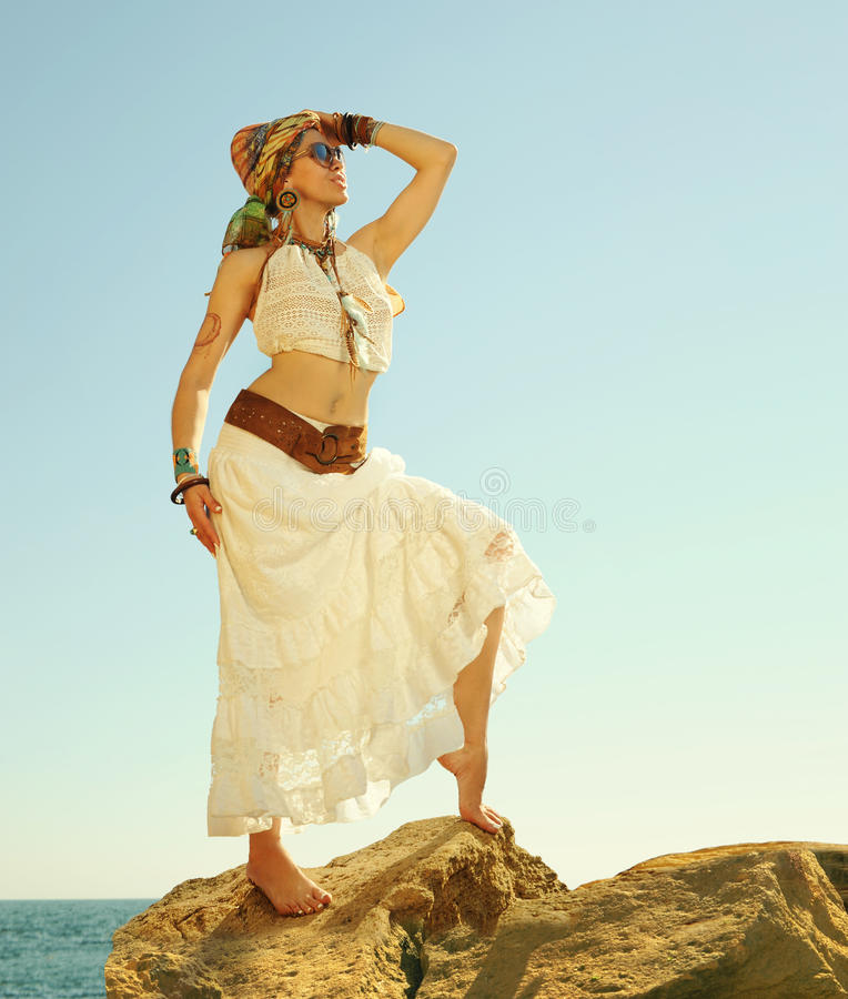 Fashion shot of a beautiful boho style woman standing on a rock near sea. Boho outfit, hippie, indie style royalty free stock photography