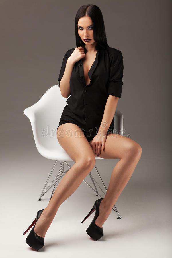 Fashion shot of a beautiful brunette woman with long straight hair, black shirt and black shoes sitting on the chair stock images