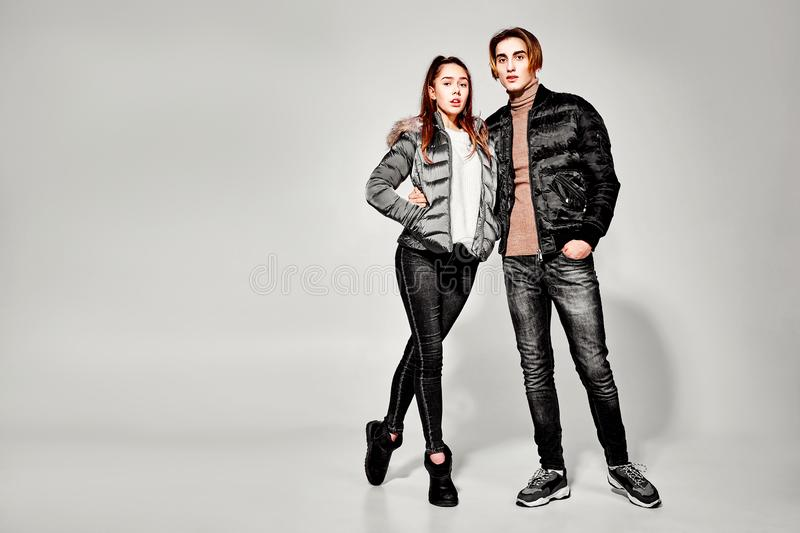 Fashion shot. Couple of young people in winter clothes posing at studio. Autumn and winter clothes royalty free stock photos