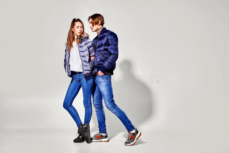Fashion shot. Couple of young people in winter clothes posing at studio. Autumn and winter clothes royalty free stock photo