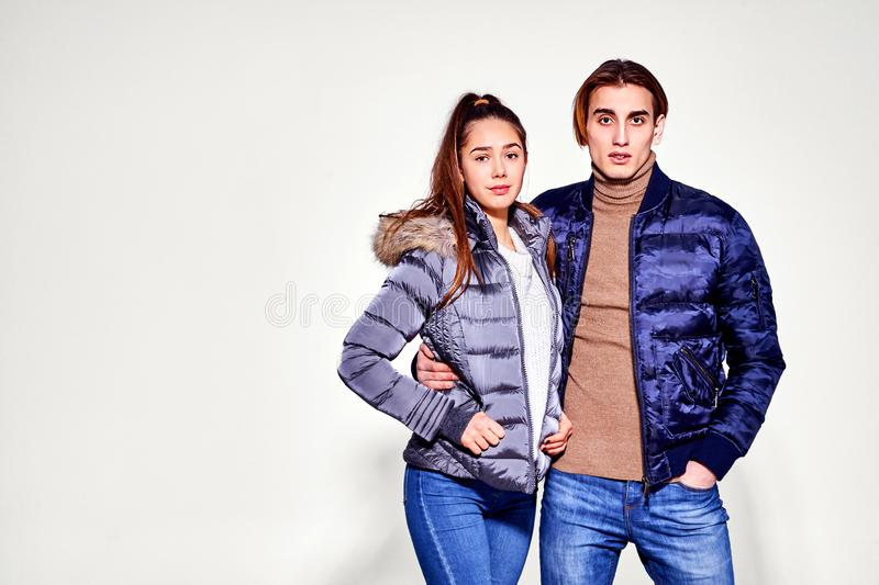 Fashion shot. Couple of young people in winter clothes posing at studio. Autumn and winter clothes stock images