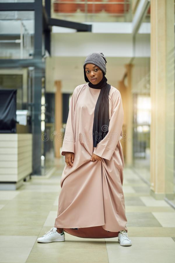 Glamorous african woman dressed in muslim style pink dress with modern hat royalty free stock photo