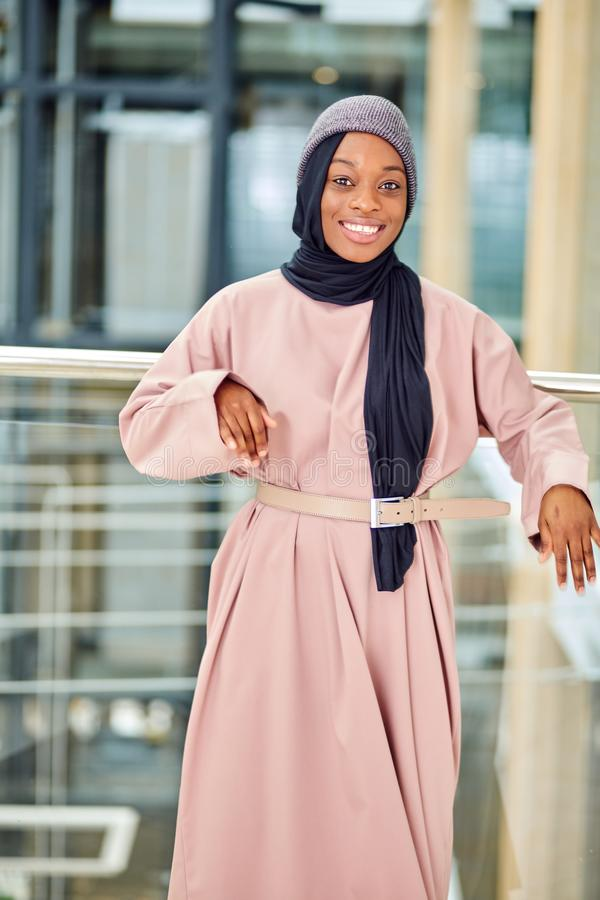 Glamorous african woman dressed in muslim style pink dress with modern hat stock photo